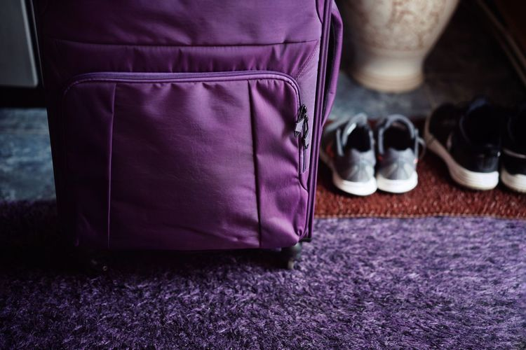 Close-up of suitcase and shoes on rug