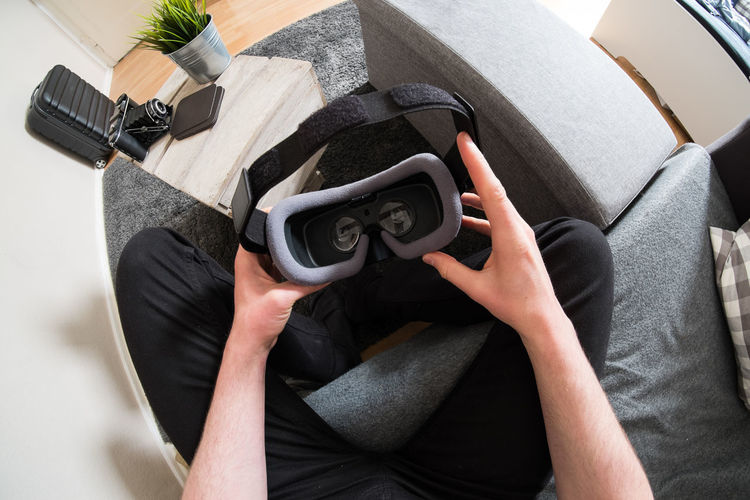 High angle view of man holding virtual reality siimulatoor while siting on sofa