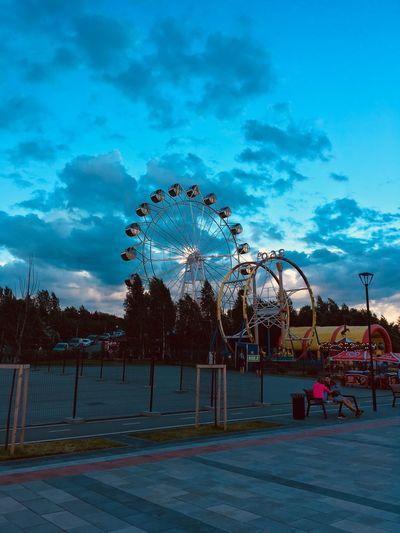 Ferris wheel in amusement park against sky