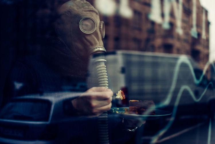 Man wearing gas mask seen through window