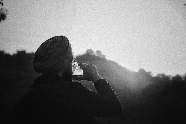Portrait of man photographing against sky during foggy weather