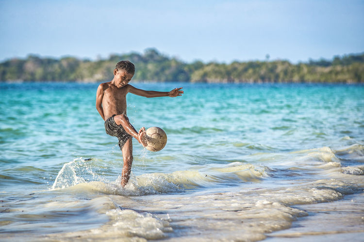 Full Length Of Shirtless Boy Kicking Ball In Sea