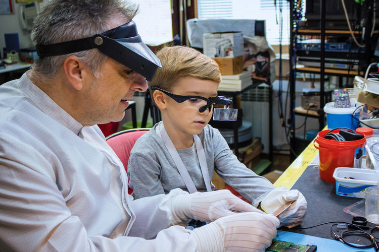 Worker teaching boy in workshop