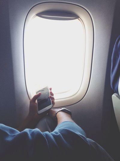 Person with smartphone near plane window