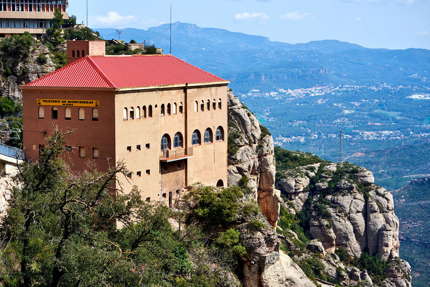 Montserrat, Spain - April 6, 2016: The Aeri de Montserrat, is an aerial cable car which provides one of the means of access to the Montserrat mountain and abbey. Spain Architecture Building Exterior Cable Car Day Editorial  Elevated Railway Faith Funicular Landmark Landscape Montserrat Monastery Mountain Nature Outdoors Overlook Pilgrimage Church Railway Santa Maria De Montserrat Scenics Sky SPAIN Sunny Day Tourism Tourist Attraction  Travel Destinations