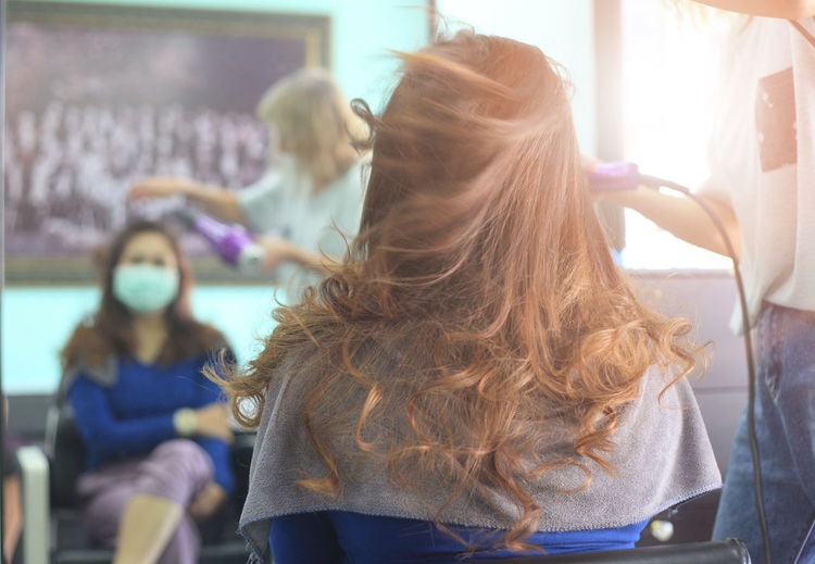 Midsection of hairdresser drying woman hair reflecting on mirror in salon