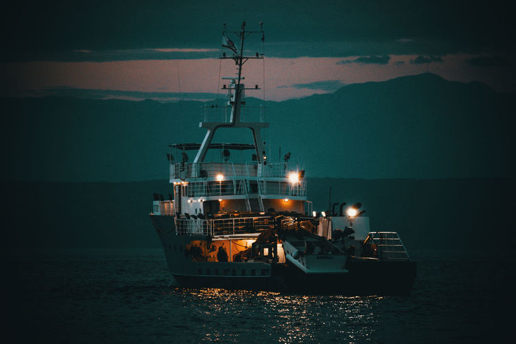 Illuminated ship in sea against sky at dusk