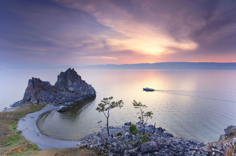 Rocky cliff on sea during sunset