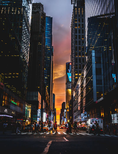 Illuminated city street by buildings against sky during sunset