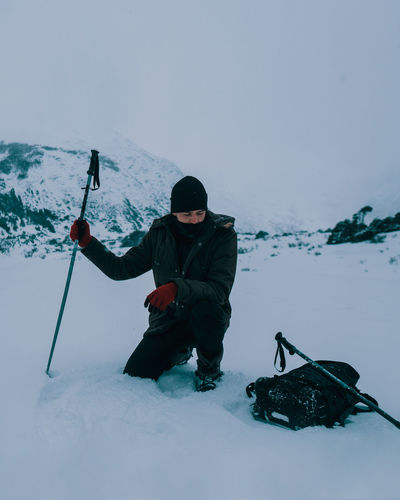 Full length of man kneeling on snow against mountains and sky during winter