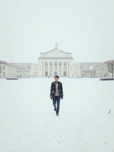 Full Length Of Man Standing On Snow Covered Field Against Built Structure