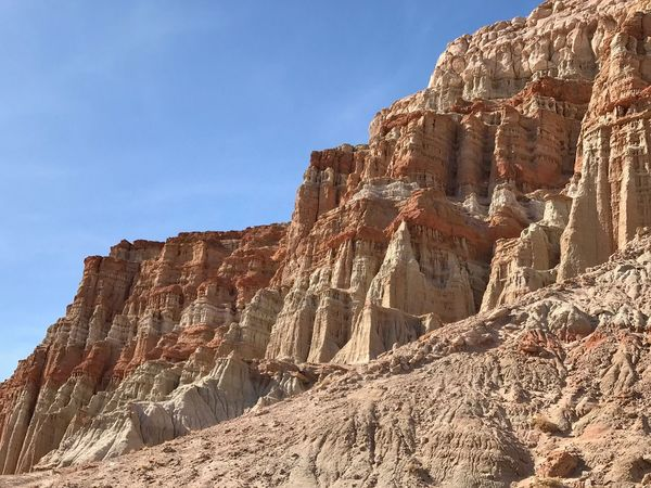 Landscape of massive vertical orange and white cliffs Red Rock Canyon State Park Rock - Object Rock Formation Geology Low Angle View No People Mountain Day Outdoors Cliff Physical Geography Travel Destinations Rock Hoodoo Sky Scenics Clear Sky Rock Face Sunlight Nature Ancient