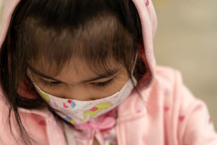 Close-up of girl wearing mask outdoors