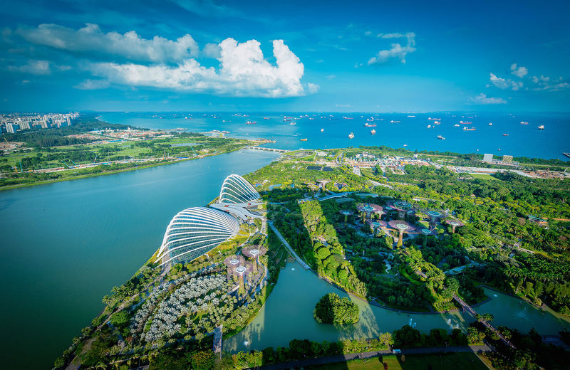 Aerial view of city by sea against blue sky