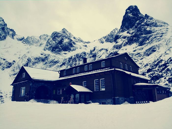 Snow covered houses and mountains against sky