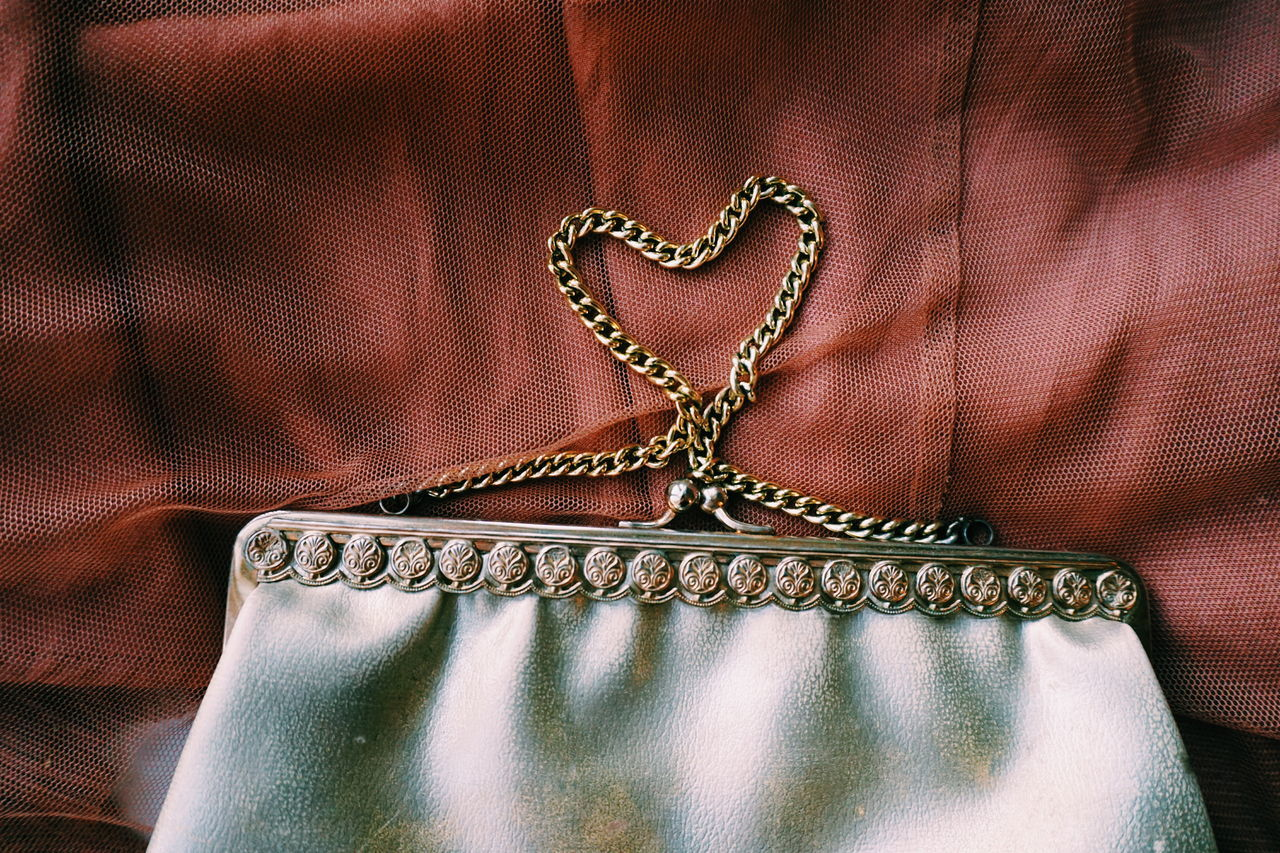 Close-up of heart shape made from purse on brown fabric