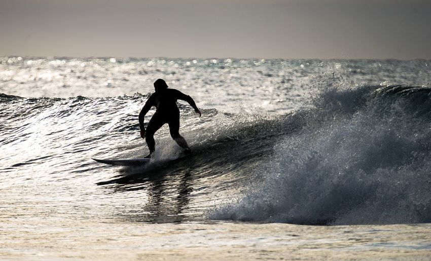 Man surfing in the sea against clear sky