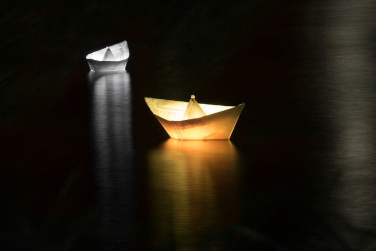Close-up of illuminated paper boat in water