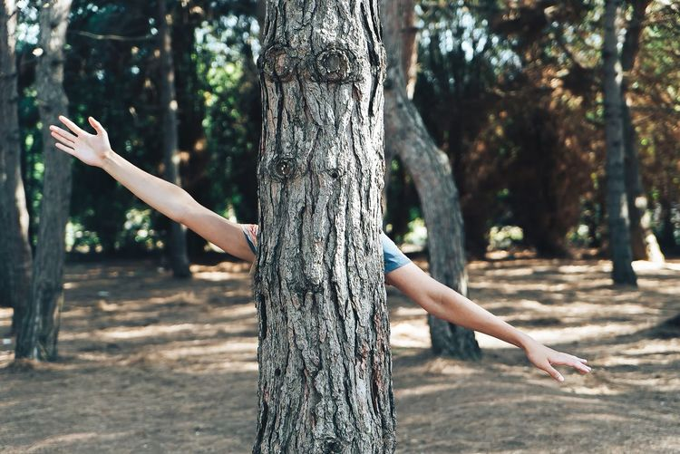 Low angle view of young woman against tree trunk