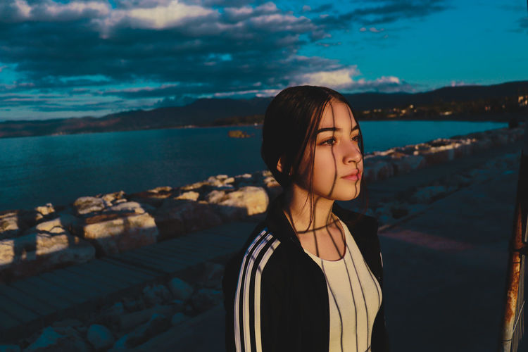 Girl looking away while standing against sea at dusk