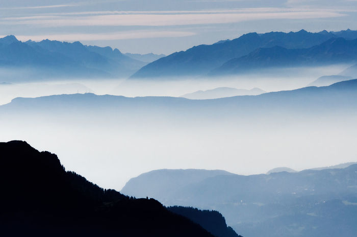 Misty mountains and hills in row in Alps, Seceda, Italy. View from above Austria Cloudscape In A Row Misty Beauty In Nature Clouds Foggy Landscape Minimalism Mist Mountain Mountain Peak Mountain Range Nature Row Silhouette Tranquil Scene Tranquility