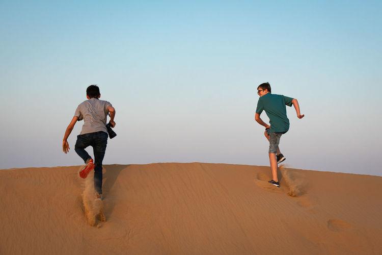 Full length of men on sand dune against clear sky