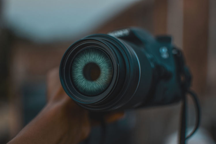 Cropped hand of man holding camera