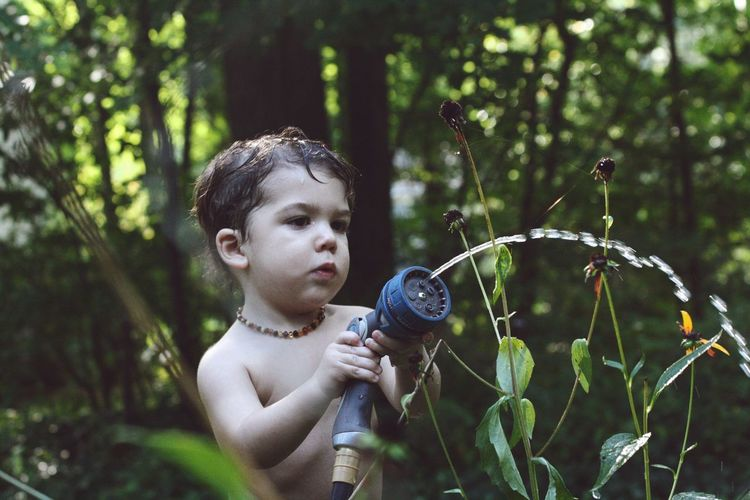 Shirtless boy holding hose by plants on field