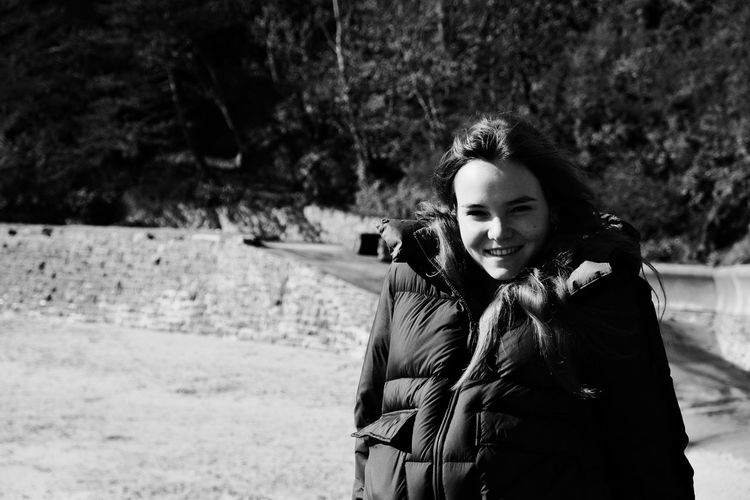 Portrait of smiling young woman in padded jacket standing outdoors