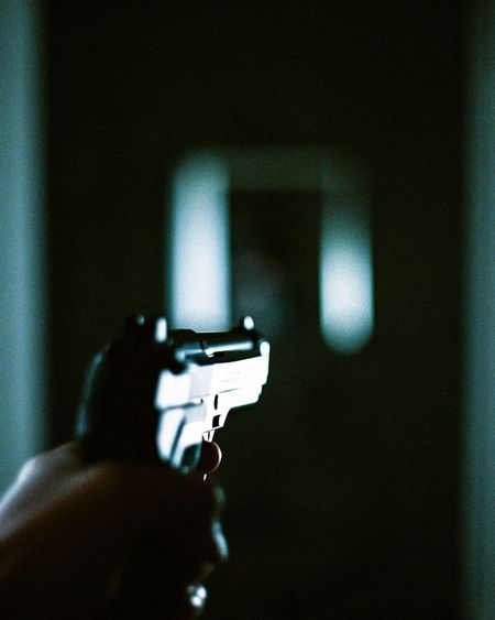 Close-up of person holding gun in darkroom