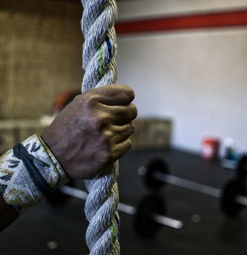Cropped Hand Holding Rope At Gym