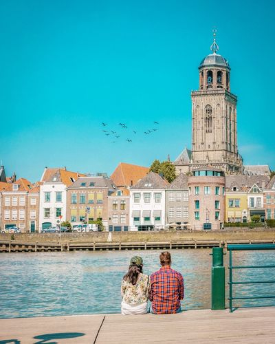 Rear View Of Couple Looking At Buildings While Sitting By River Against Clear Blue Sky In City