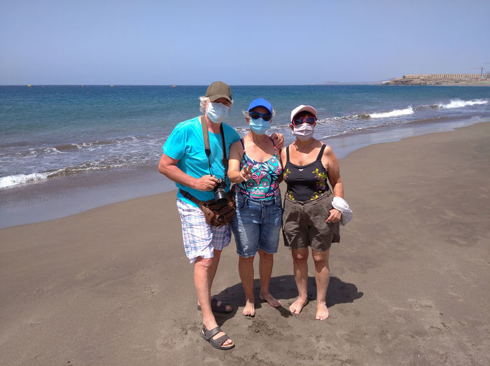 People with mask standing on beach