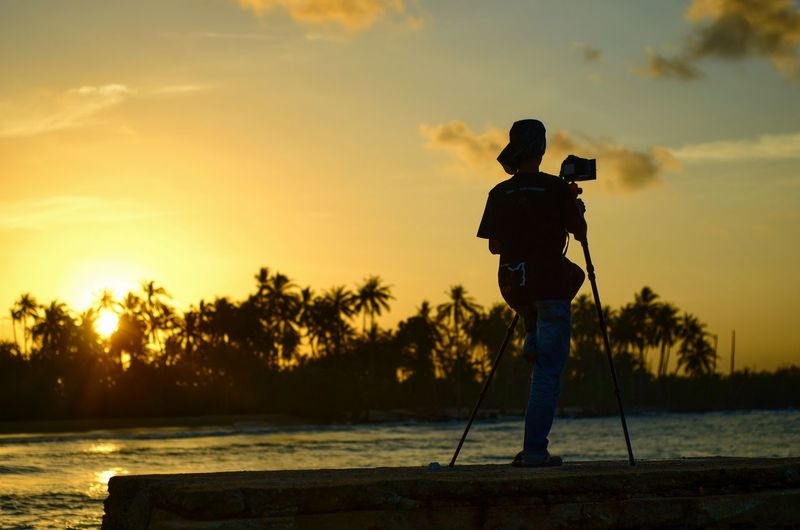Scenic view of photographer silhoutte on the sunset background. Wallpaper Background Malaysia Beach ASIA Silhoutte Scenic Photographer Scenics Amazing Tripod Camera DSLR Action Alone Man Beach