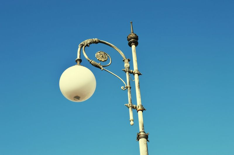 Low angle view of lamp post against clear blue sky