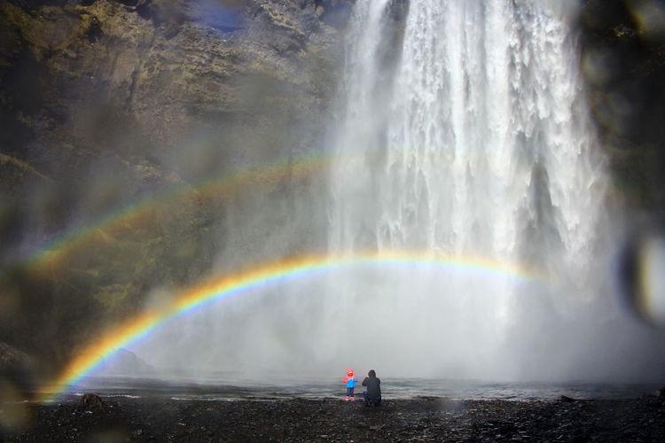 Scenic view of rainbow over waterfall