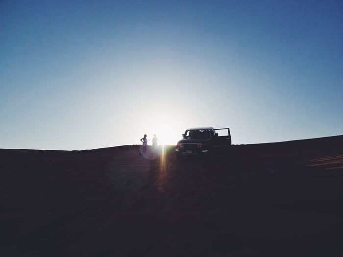 Women Standing By Off-Road Vehicle Against Blue Sky
