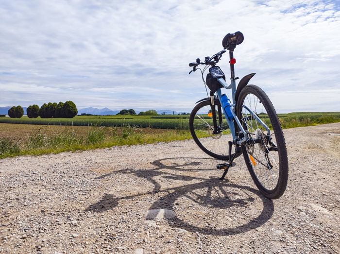 Bicycle on road by field against sky