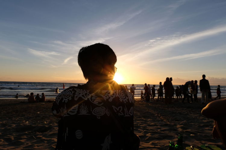 Rear view of young man sitting at beach against sky during sunset