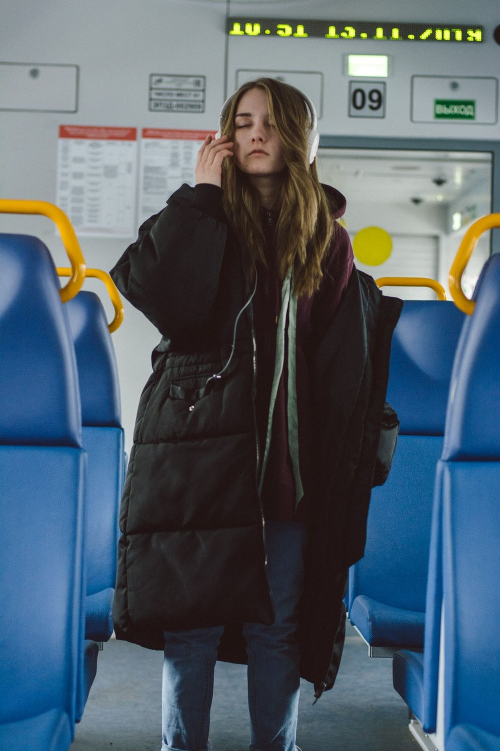standing, one person, indoors, three quarter length, real people, lifestyles, public transportation, women, front view, transportation, technology, leisure activity, smiling, mode of transportation, young adult, clothing, casual clothing, travel, hairstyle