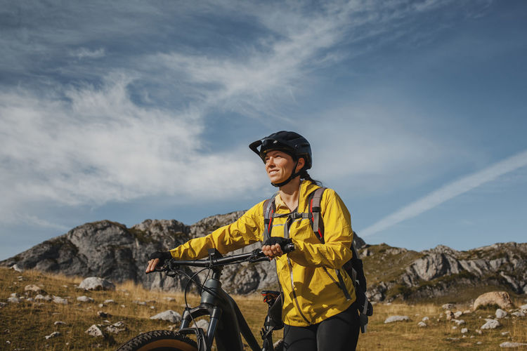 Young man with bicycle standing on mountain against sky