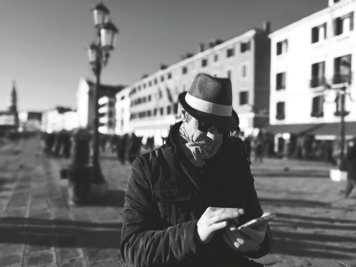 Man in hat using mobile phone in city