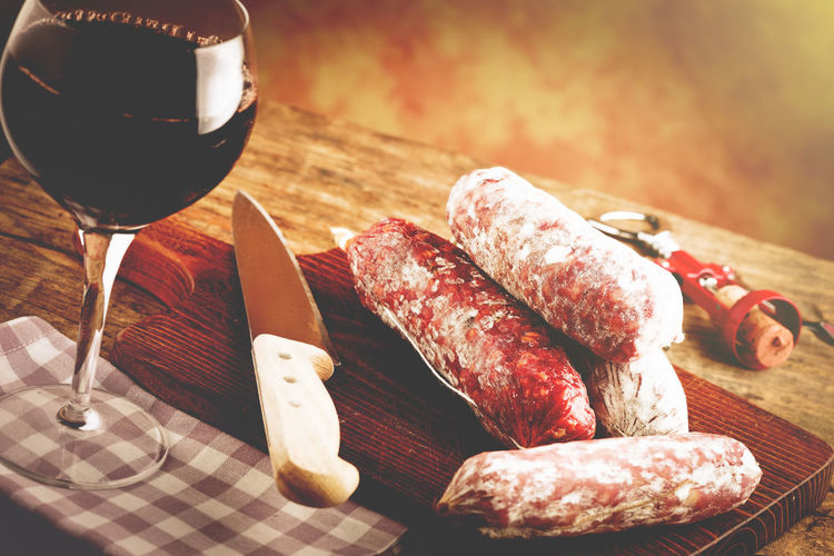Close-up of red wine glass and salami on table