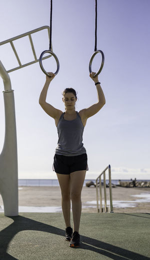 Full length of woman standing exercising against sky