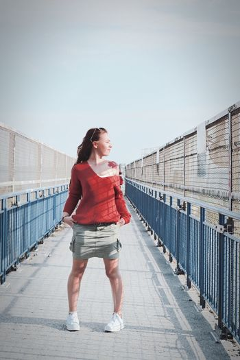 Full length of woman standing on bridge against sky