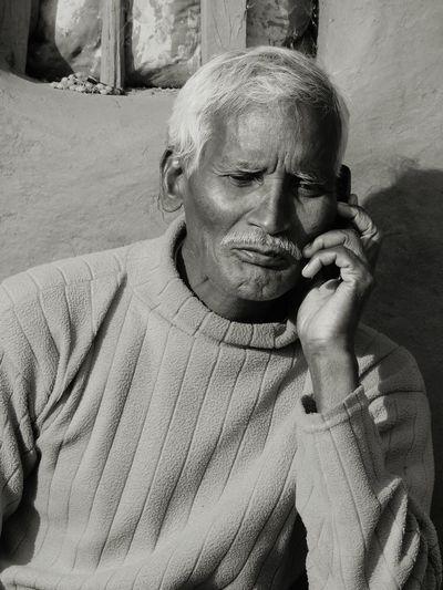 Thoughtful Senior Man Sitting Against Wall
