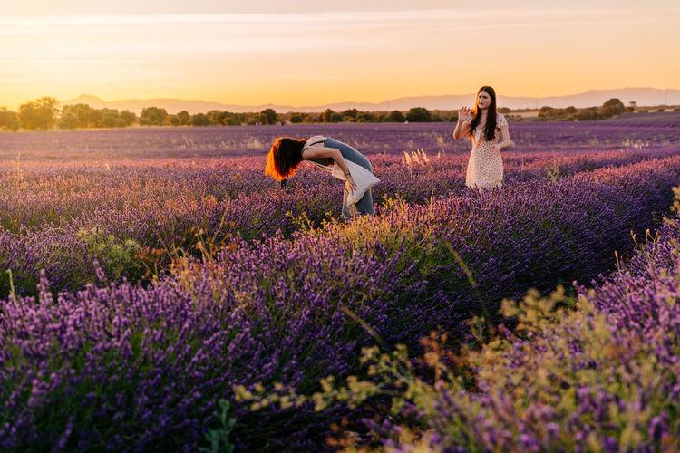 Full length of women standing on flower field