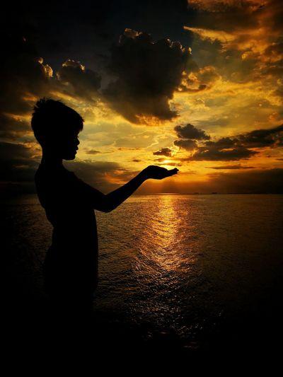 Optical Illusion Of Silhouette Boy Holding Sun At Beach Against Orange Sky