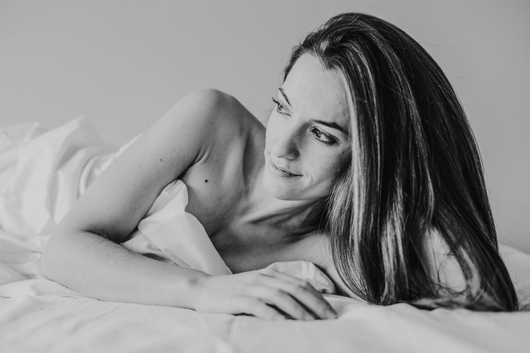 Thoughtful woman lying down on bed