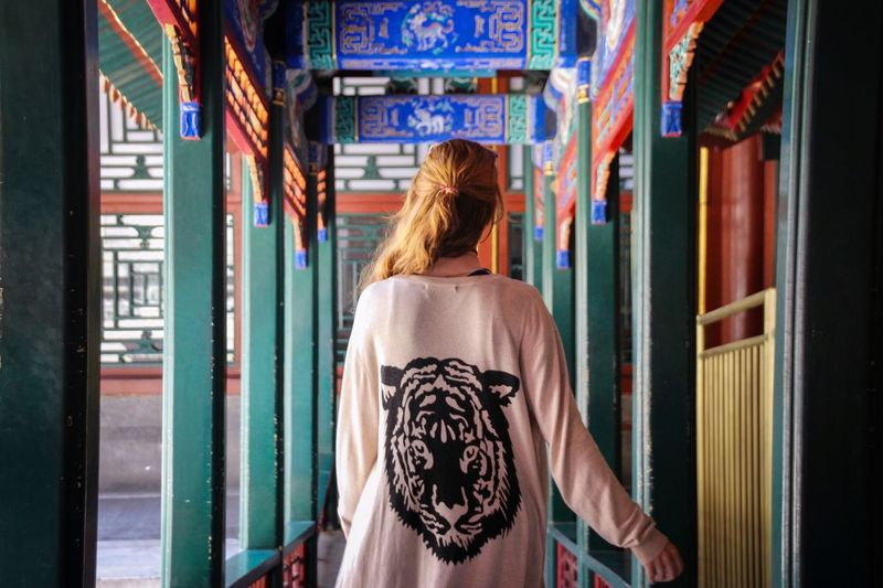 Rear View Of Woman Walking In Corridor Of Temple